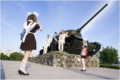 Students picture themselves on a Red Army tank-monument in Tiraspol, Transnistria